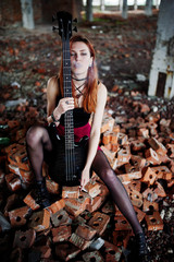 Red haired punk girl wear on black and red skirt, with bass guitar at abadoned place. Portrait of gothic woman musician. Smoking cigarette.