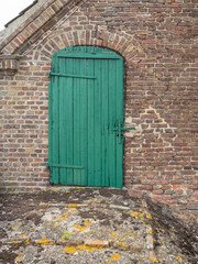 Old green wooden door on a brick barn