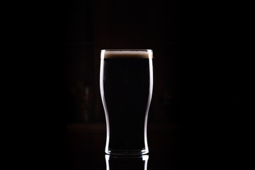 Obraz Stout (Guinness like) Beer in pint glass, silhouette with perfect head and dark background - fototapety do salonu