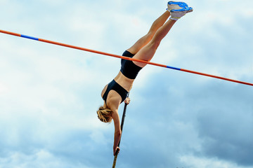 competition pole vault jumper female on blue sky background
