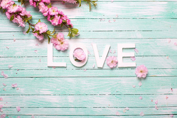 Word love and  border from pink almond flowers on turquoise wooden background.
