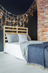 Bed with decoration next to brick wall