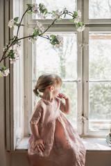 Kleines Mädchen in Kleid guckt aus dem Fenster