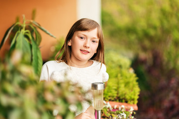 Portrait of sweet little girl resting on the balcony on a nice warm day
