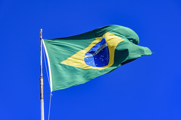 Brazilian flag fluttering in the wind and the blue sky in the background