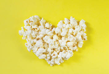 Love cinema concept of popcorn. Heart shaped white fluffy popcorn on yellow retro background