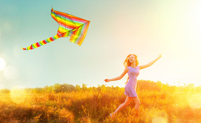 Beauty girl in short dress running with flying colorful kite over clear blue sky