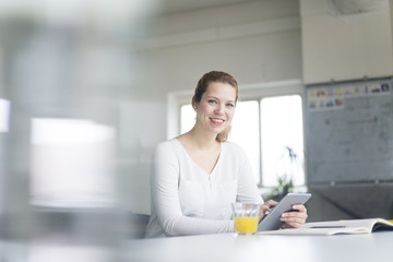 Businesswoman working at desk in her office, using digital tablet