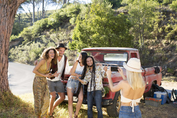 Young woman taking cell phone picture of friends outside pick up truck