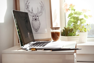 Creative workplace with laptop near windowsill in modern room