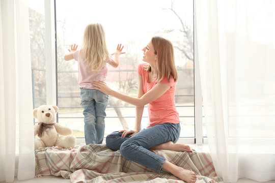 Mother and daughter near window in room