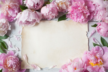 Pink peonies on a wooden background and a paper blank sheet