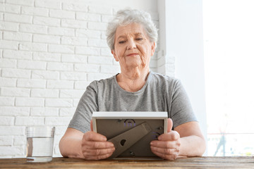 Elderly woman sitting at table with photo frame and glass of water. Concept of retirement