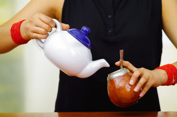 Woman holding white small jar pouring hot water into traditional cup with typical metal straw sticking up, preparing popular drink called mate