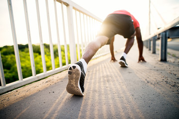 African american fitness handsome man training. Jogging and stretching outside at morning sun. Healthy lifestyle concept.