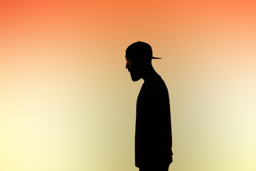 Side view of silhouette man against orange background