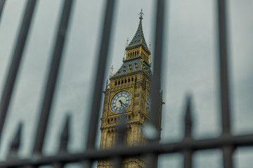 Special view of the Big Ben tower seen behind bars on a dark day