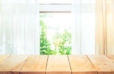 Empty of wood table top on blur of curtain window and abstract green from garden with sunlight .For montage product display or key visual layout