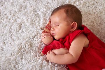 sleeping newborn in red dress