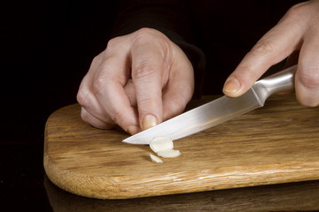 Woman chopping garlic with a knife