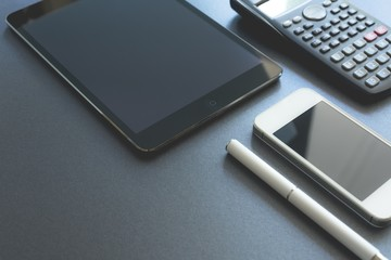 A few electronic devices displayed on grey background. Smart phone, pad and calculator, all digital except a pen. Scene workplace.