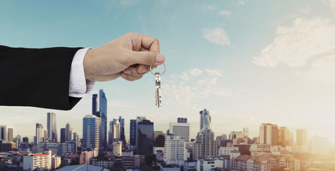 Hand holding keys with city background