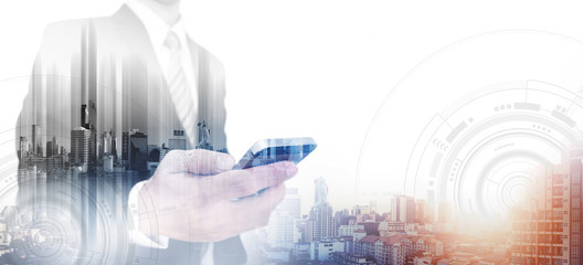Double exposure businessman using smartphone and city in sunrise, with white copy space
