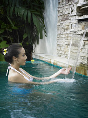 profile of a woman enjoy water falling in the spa pool