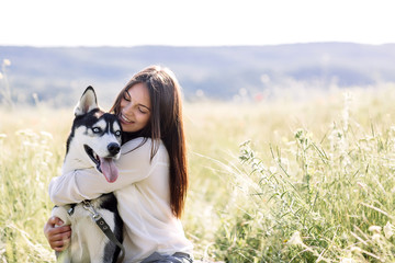 Beautiful girl plays with a dog (black and white husky with blue eyes) green field