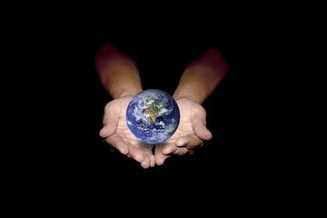 Blue earth in human hands isolated on black background.