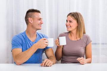 Young happy couple enjoys drinking coffee  together.