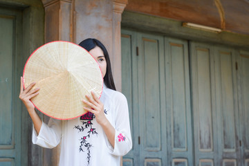 Beautiful women Vietnam with white ao dai dress in old city , selective and soft focus of face color vintage style