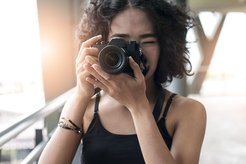 young woman using a camera to take photo outdoors at balcony building