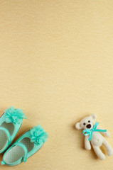 Baby background with bear toy and turquoise shoes for baby girl