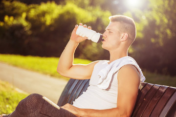 Young man drinking water while resting from  exercise.