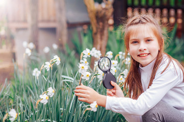 beautiful little girl looking through a magnifying glass on the flowers