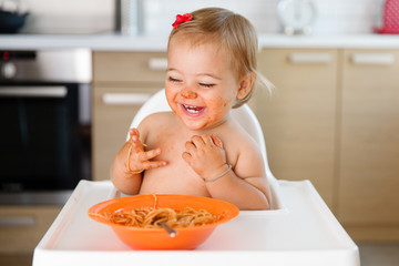 laughing toddler with messy face eating pasta