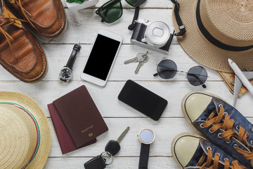 Top view women and man accessories to travel concept.White and black mobile phone,airplane,hat,passport,watch,sunglasses,shoes and key on wood table.