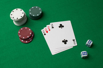 Playing cards, chips and dice on green background