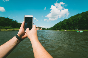 mans hands hold phone, taking picture of the lake