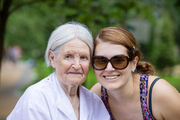 Adult granddaughter and senior grandmother smiling outdoors