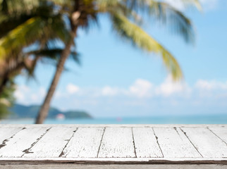 Wood table top and blurred summer beach with coconut tree and blue sky background. - can used for display or montage your products.