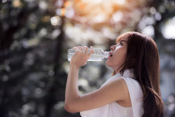 Young girl drinking water during morning jogging