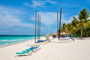 Wall Mural - Varadero beach in Cuba with sailboats and thatched umbrellas