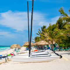 Fototapete - Varadero beach in Cuba with sailboats and thatched umbrellas