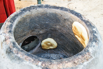 Traditional way of baking bread in the tandoor in Tunissia. Bread in the tandoor. Summer 2015.