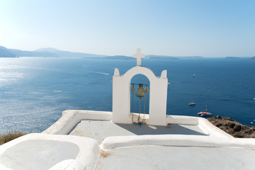 Beautful white chapel at Santorini and in the background the view of caldera