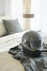 Motorcycle helmet and leather jacket setting on bed in modern bedroom
