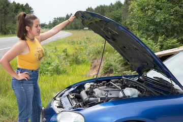 Woman leaning over looking into the engine compartment of a broken down car