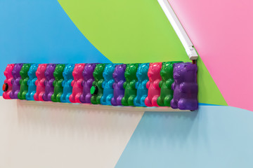 Gummy bears attached to colorful wall